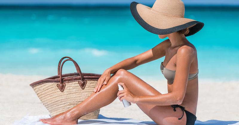 une femme s'applique de la crème solaire