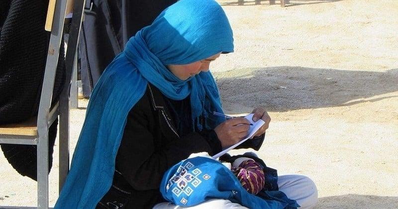 Cette photographie d'une Afghane, bébé dans les bras et stylo en main, symbole d'une détermination sans faille, fait le tour de la toile