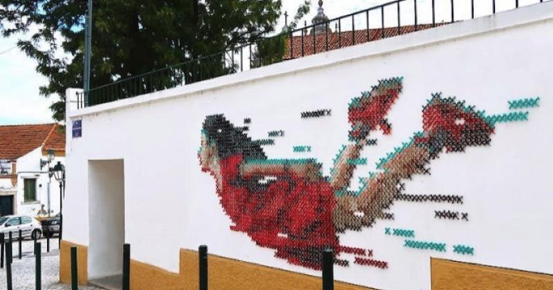 Cette oeuvre de street art a été brodée sur un mur à l'aide de vis et de fil