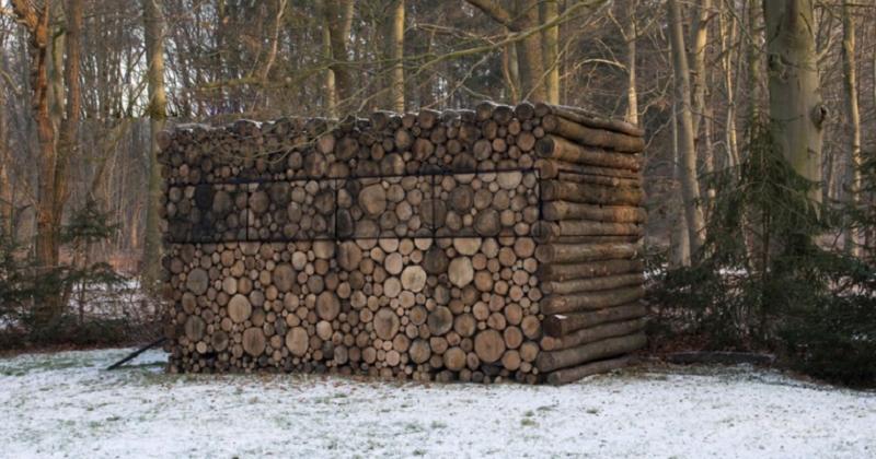 Une pile de bois cache un studio moderne à l'intérieur